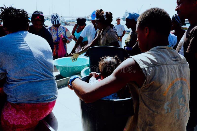 lokala byinvånare väntar på fiskebåtarna för att ankomma på morgonmarknaden av staden royaltyfri fotografi