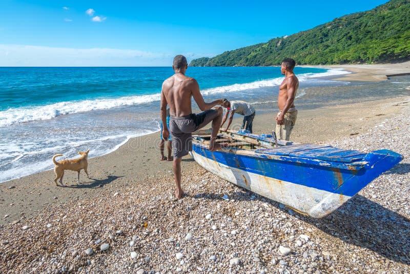 Lokala fiskare på Playa San Rafael, Barahona, Dominikanska republiken som förbereder deras fartyg för att fiska arkivbild