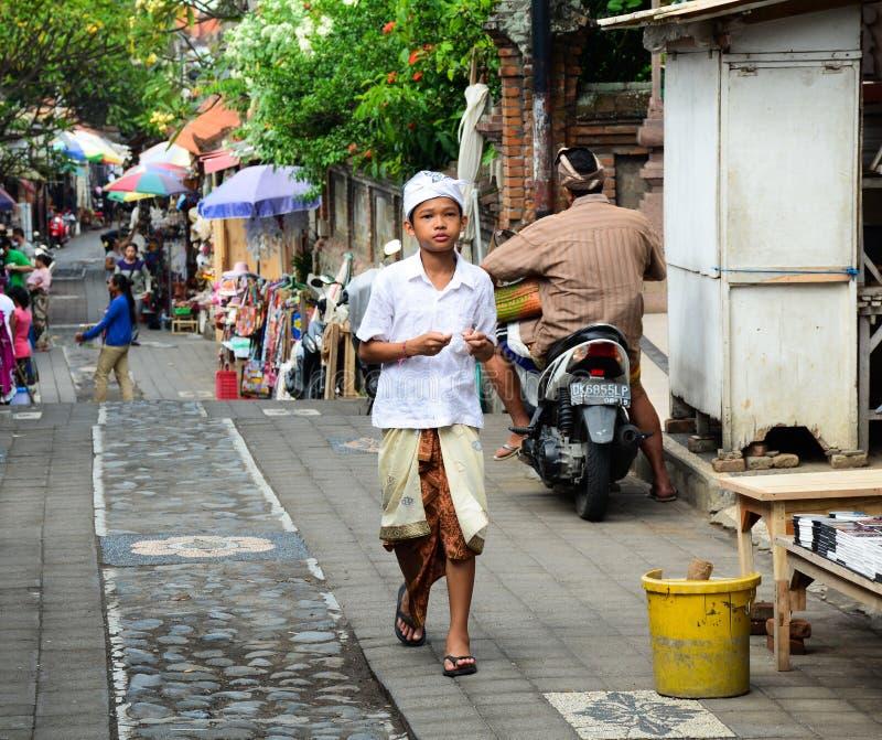 Lokala pojkar som går på gatan i Bali, Indonesien arkivbilder