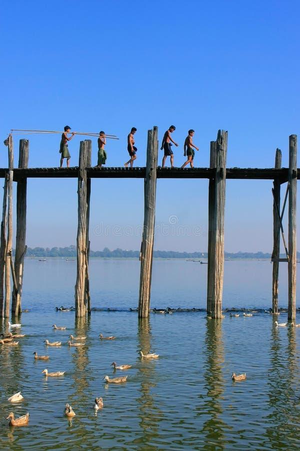 Lokala ungar med fiskepoler som går på bron för U Bein, Amarapur arkivbild