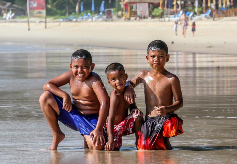 Lokale Aziatische kinderen op het strand Drie jongens die in de golven spelen royalty-vrije stock afbeelding