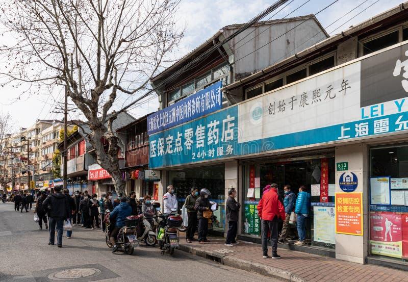 Lokale bewoners staan in een lange rij om gezichtsmaskers te kopen in een drugshandel tussen de uitbraak van Covid-19 coronavirus stock foto