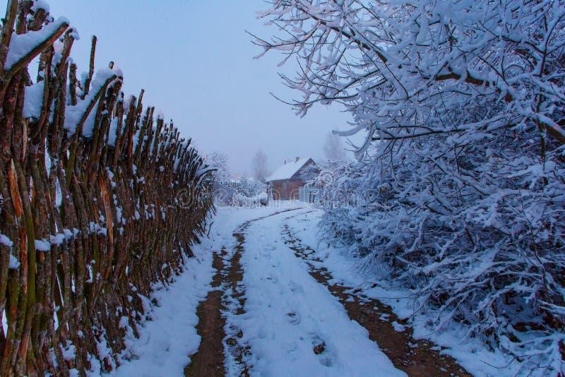 Lokale de winterweg die tot klein buitenhuis leiden Sneeuwlandschap stock foto's