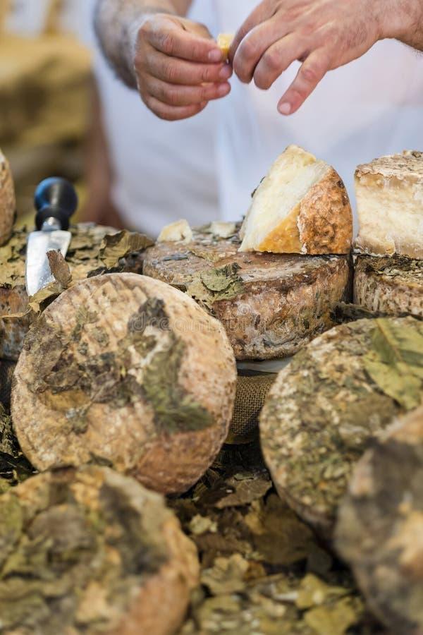 Lokale Feinkostgeschäftarbeitskraft, die Käse schneidet lizenzfreie stockfotos