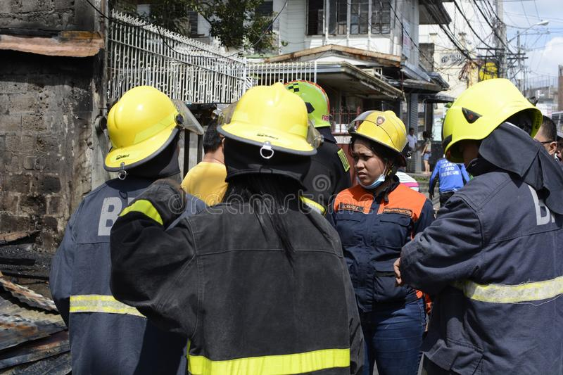 Lokale firewoman mensenhulp op de redding van de noodsituatiereactie tijdens huisbrand die binnenlandse barakhuizen uithaalde stock foto