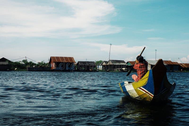 lokale Frau, die den See auf seinem Kanu vor der sich hin- und herbewegenden Pfahlhausregelung kreuzt stockfoto