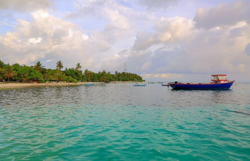 Lokale haven in Indische Oceaan, de Maldiven Dhangethieiland Kleine boten op turkoois oceaanwater op blauwe hemel met witte wolke royalty-vrije stock foto