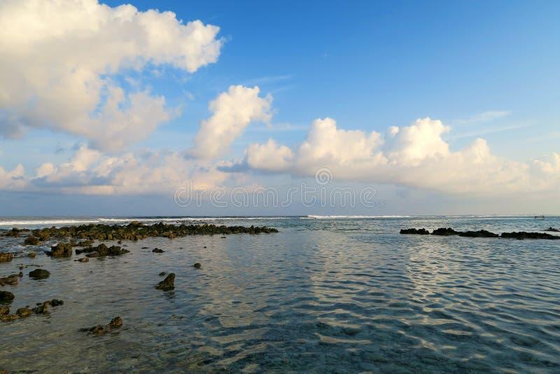 Lokale het surfen vlek op Himmafushi-eiland, de Maldiven: wolkenbezinning in oceaan stock foto's