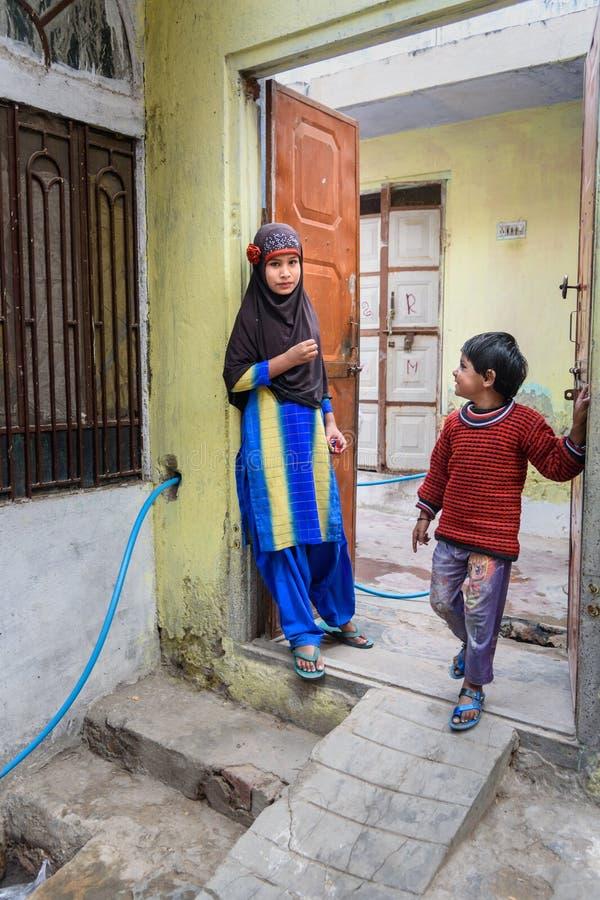 Lokale Indische meisje en jongen die zich bij de deur van huis in Amer bevinden Rajasthan India royalty-vrije stock fotografie