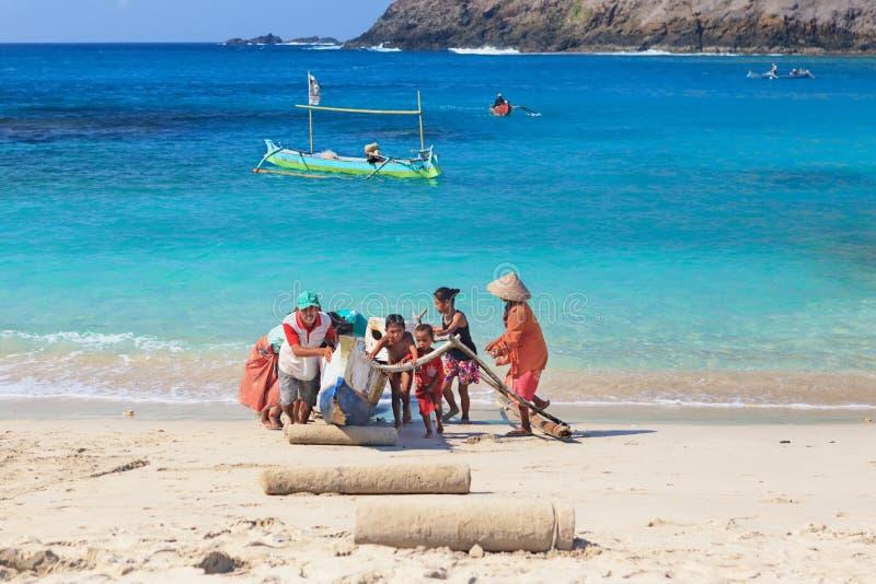 Lokale Kinder helfen Eltern, traditionelles Fischerboot heraus zu schleppen lizenzfreie stockfotografie