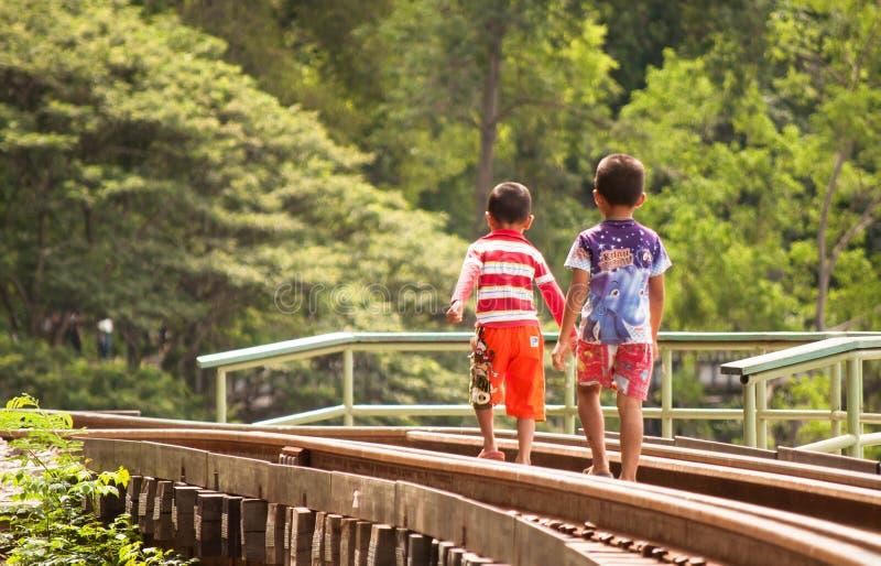 Lokale kinderen die op de spoorweg in Kanchanaburi lopen stock foto's