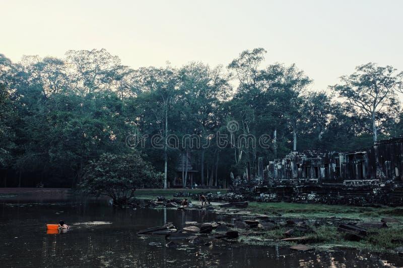 lokale Leute, die nach kleinen Fischen an einem See nahe bei den Bauerben mit etwas Ruinen suchen stockfoto
