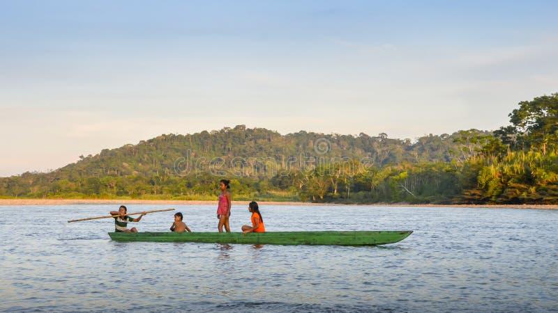 Lokale Quechua stamtieners in Ecuatoriaans Amazonië op een kano op de rivier Napo stock foto