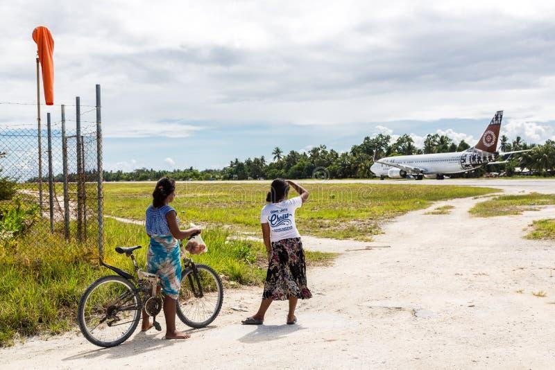 Lokale tieners met een fiets die een het vertrekken vliegtuig, het atol van Zuidentarawa, Kiribati bekijken stock foto