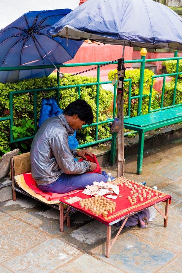 Lokale verkoper die geld ruilen aan muntstukken bij de ingang van Aaptempel Swayambhunath Stupa, Katmandu, Nepal stock foto's