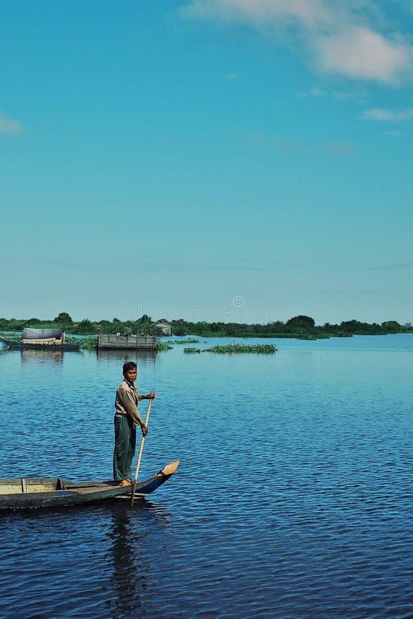 lokale visser die zich bij de boog van zijn kano bevinden terwijl het paddelen over het overstroomde meer rond de onwettige regel royalty-vrije stock afbeeldingen