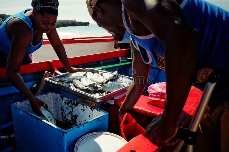 lokale visser die zijn vangst ontladen terwijl de vrouw van de markt doorgaat om zijn vissen te controleren stock fotografie