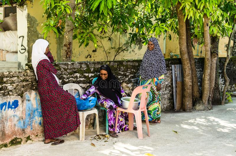 Lokale vrouwen in heldere nationale kleren op de straat van een klein tropisch eiland Het Eiland van Kudahuraa, de Maldiven royalty-vrije stock foto