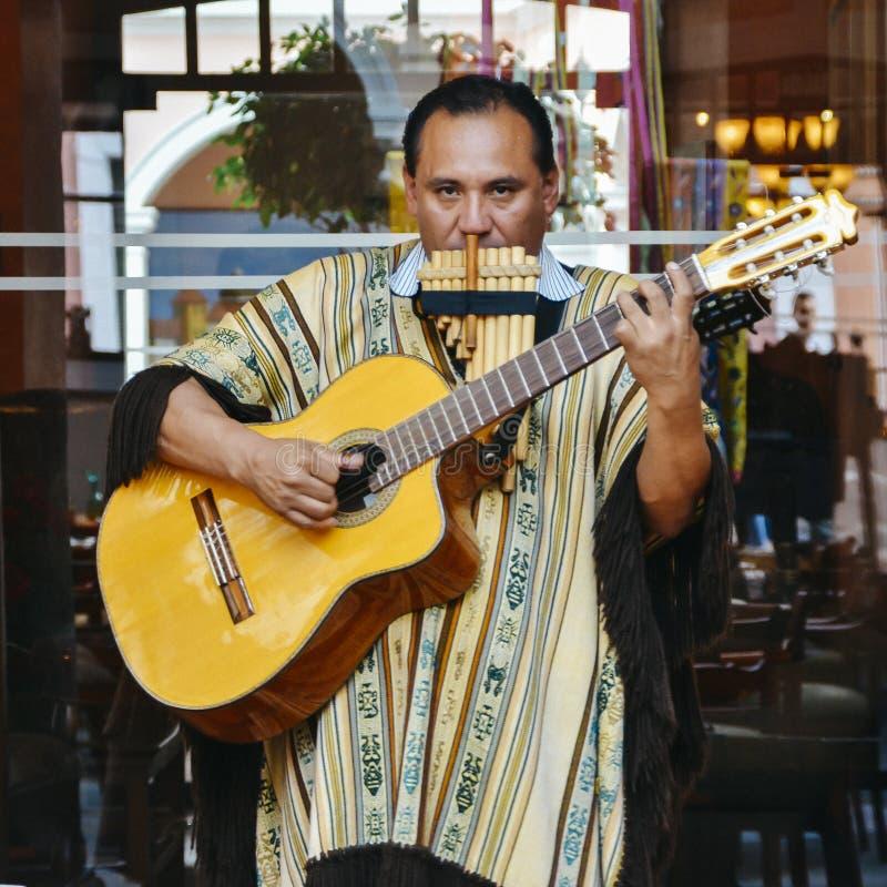 Lokaler ekuadorianischer Mann spielt Gitarre und Flöte auf der Straße stockbilder