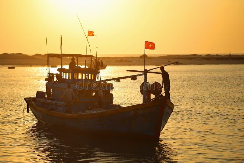 Lokaler Fischer, der an Fischerboot Vietnams an einem sonnigen Morgen arbeitet stockbild