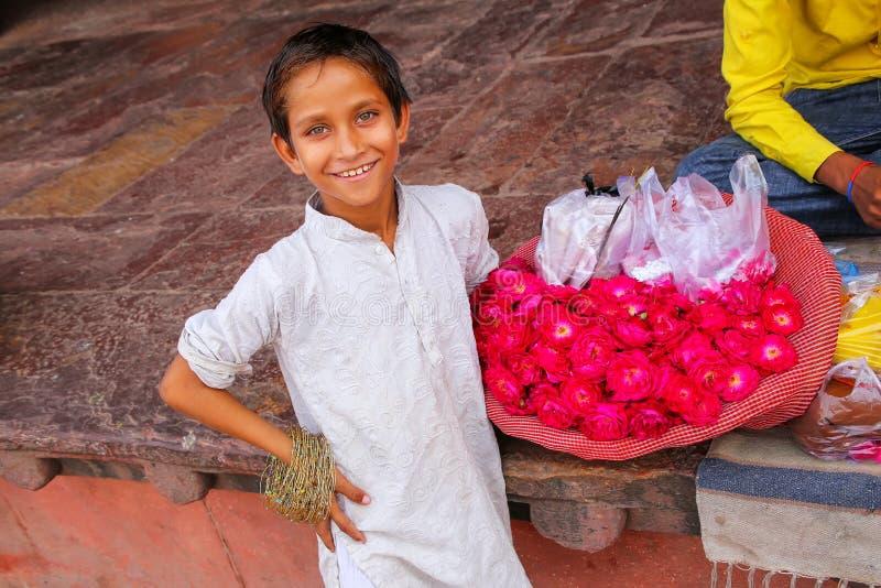 Lokaler Junge, der Blumen im Hof von Jama Masjid im Fett verkauft lizenzfreie stockfotos