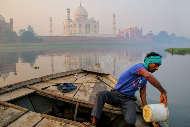 Lokaler Mann, der Wasser aus dem Boot auf Yamuna-Fluss heraus nahe Taj freikauft stockbilder