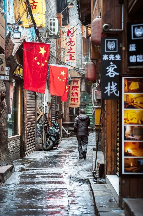 Lokaler Mann geht entlang eine Gasse von Bars und von Vereinen in Fenghuang, C stockbilder