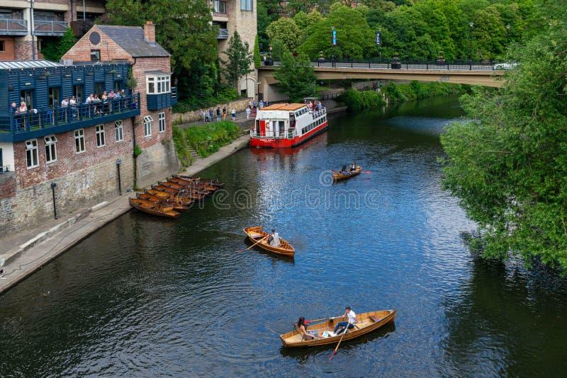 Lokaler och turister som njuter av solsken vid floden Wear i Durham arkivfoto