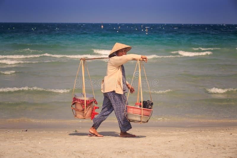 Lokaler Verkäufer mit Waren in den Körben geht entlang Ozean-Strand lizenzfreie stockbilder