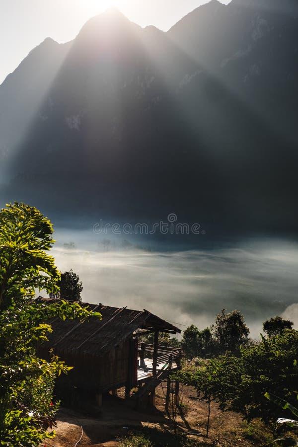 Lokales Haus im ländlichen Hochland mit Seenebel und -hellem Sonnenschein strahlt über Berg in Chiang Mai, Thailand aus lizenzfreie stockfotografie