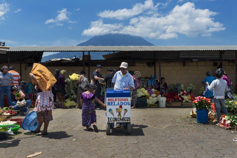 Lokales Mädchen, das kaufende Eiscreme der traditionellen Kleidungs in einem Straßenmarkt in der Stadt von Antigua, in Guatemala, lizenzfreie stockfotos