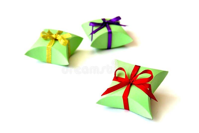 Lokalisiert drei apfelgrünen Papiergeschenkboxen für Schmuck mit den roten, violetten, goldenen Satinbandbögen auf weißem Hinterg stockfoto