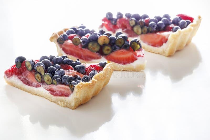 Lokalisiert drei Stück des scharfen Kuchens des Ricotta mit frischer Erdbeere, Blaubeere und Himbeere stockbild