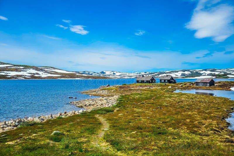 Lokalisierte Häuser umgeben durch schöne Landschaft von den Hügeln und von Berg teilweise bedeckt mit weißem Schnee, Norwegen lizenzfreie stockbilder