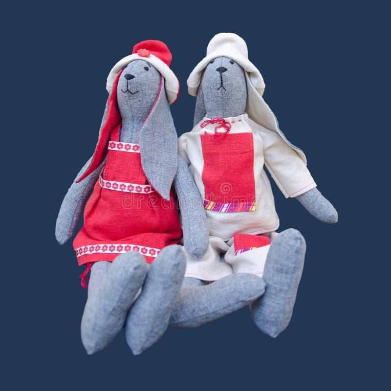 Lokalisierte handgemachte Puppenhäschenfamilie in schlichtem Kleidung sittin stockbild