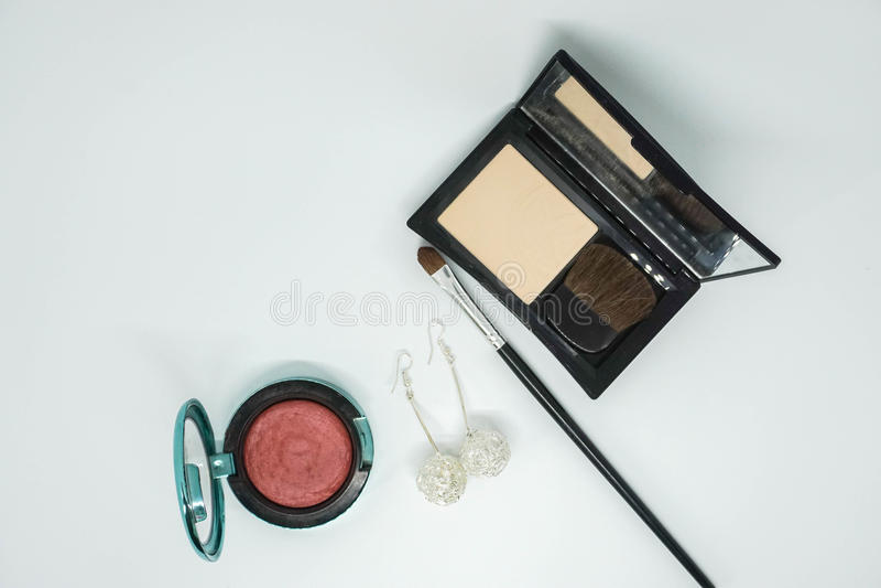 Lokalisierte Kosmetik, Lidschattenpinsel und Pulver im schwarzen Luxuskasten und mit Ohrringen für Frauen lizenzfreie stockfotos