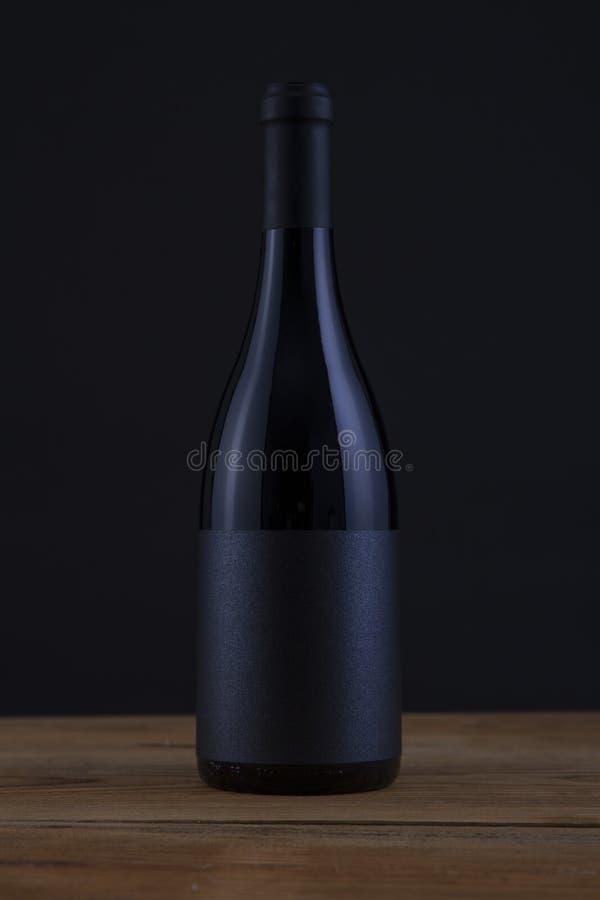 Lokalisierte Rotwein-Flasche in einem schwarzen Hintergrund und in einem schwarzen Aufkleber lizenzfreies stockfoto
