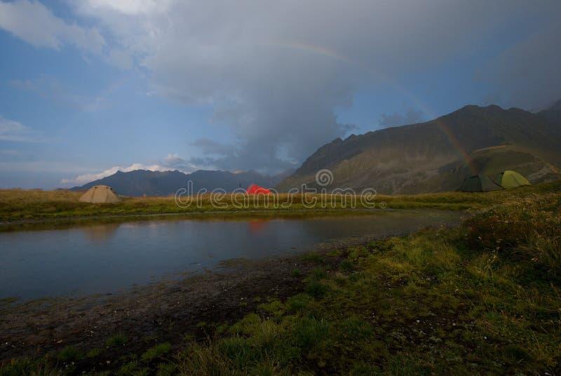Lokalisierte Zelte in den Alpen im Regenbogen lizenzfreie stockbilder