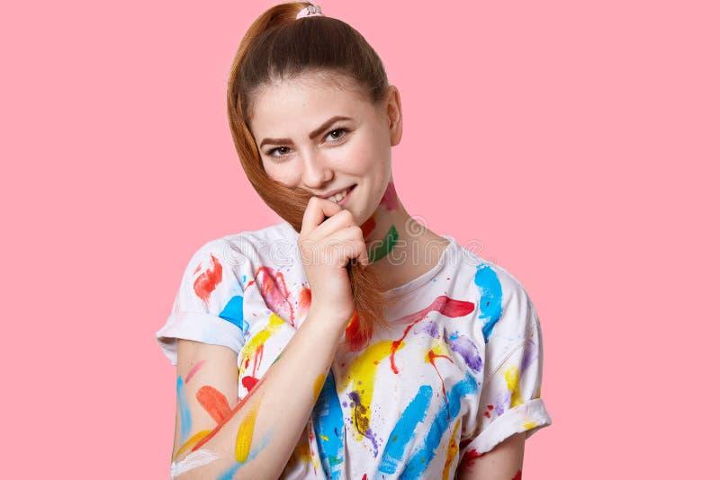 Lokalisierter Schuss der erfreuten künstlerischen Frau mit dem Pferdeschwanz, hat T-Shirt mit Watercolours, hat creatie Besetzung lizenzfreie stockfotos