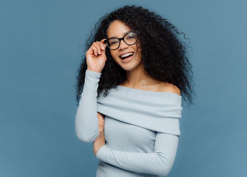 Lokalisierter Schuss der lächelnden jungen Afroamerikanerfrau berührt Rahmen von Gläsern, hat frohen Ausdruck, trägt stilvollen P lizenzfreies stockfoto