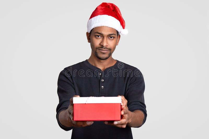 Lokalisierter Schuss des ernsten schwarzen Mannes trägt Santa Claus-Kopfbedeckung, trägt wenig Kasten des Geschenkes, gekleidet i stockfoto