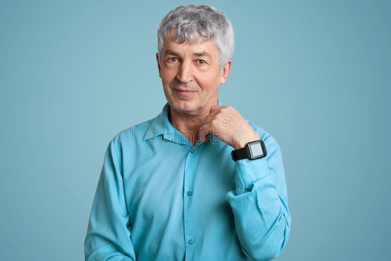 Lokalisierter Schuss des hübschen älteren Mannes trägt blaues elegantes Hemd, Armbanduhr, hat geknittert Gesicht, Haltungen über  lizenzfreies stockfoto