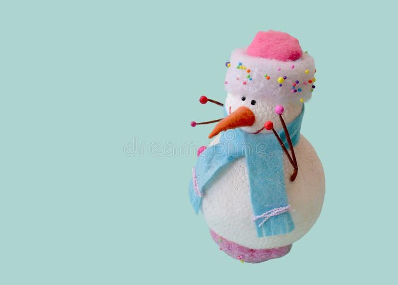 Lokalisierter Spielzeugschneemann in einem rosa Hut und in einem blauen Schal lizenzfreies stockfoto