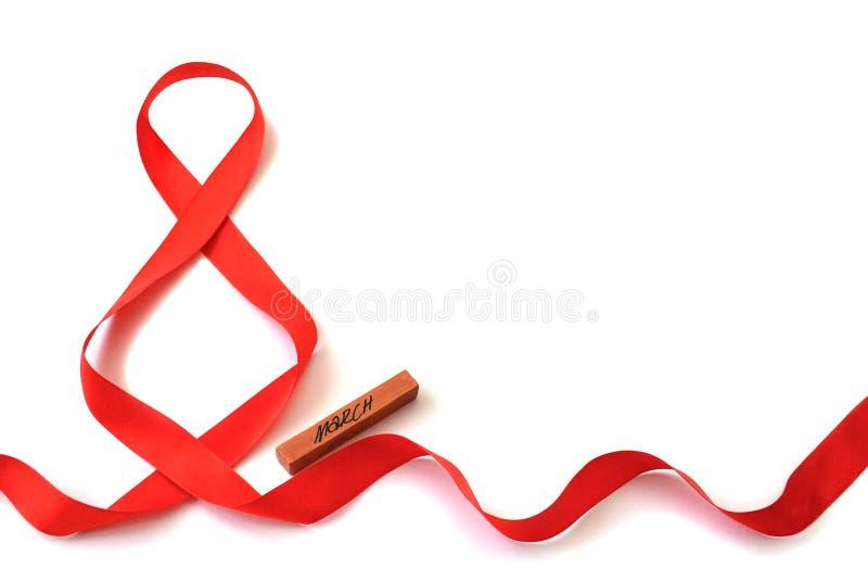 Lokalisiertes helles rotes Satinband in Form des Abbildung 8 und eine hölzerne Stange mit der Aufschrift 'März 'auf einem weißen  stockfotos