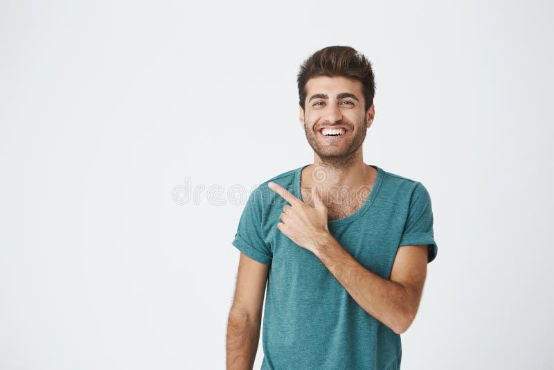 Lokalisiertes Studioporträt des glücklichen attraktiven kaukasischen Kerls im zufälligen blauen T-Shirt, wenn die modische Frisur stockbild