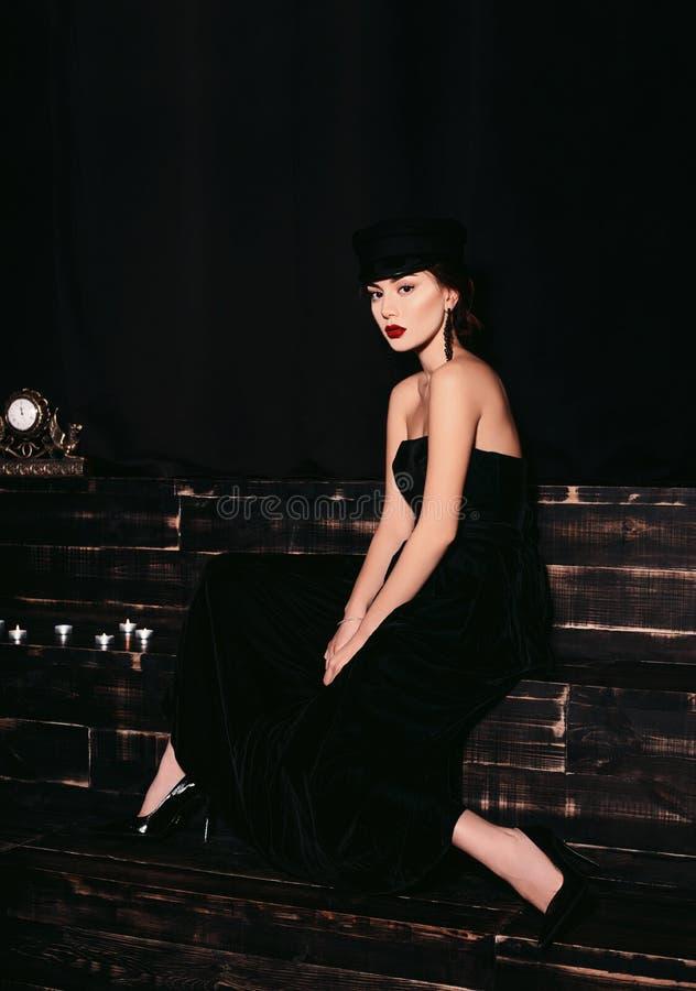 Lokalisiertes Zauberporträt eines sexy und heißen Modells, das auf hölzerner Treppe im Studio mit einem schwarzen Hintergrund sit lizenzfreies stockbild
