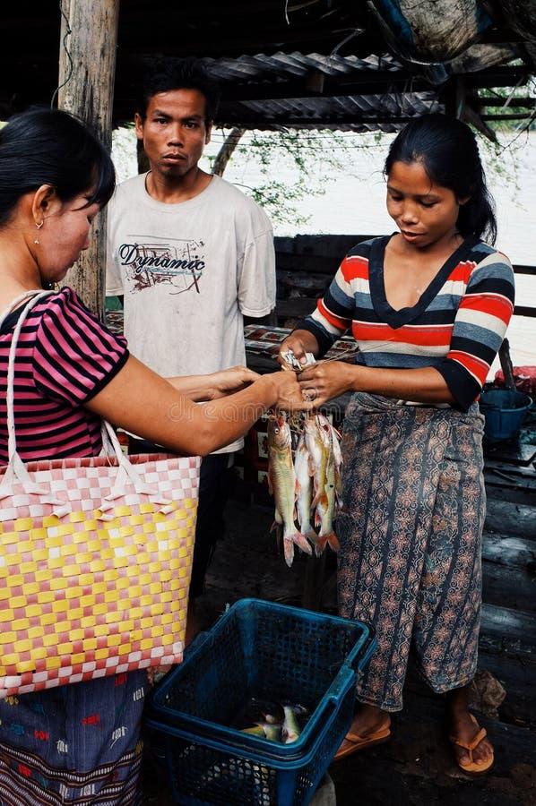 lokalna młodej kobiety sprzedawania ryba przy wioska rynkiem z jej mężem zdjęcie royalty free