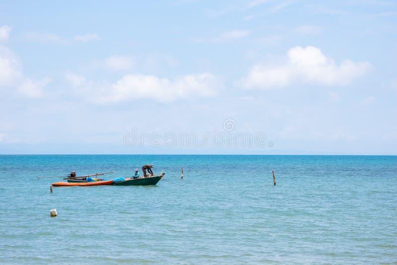 Lokalne rybak łodzie na lewej stronie unosi się nad morzem z jaskrawym niebem w tle w popołudniu przy Koh Mak wyspą zdjęcia stock