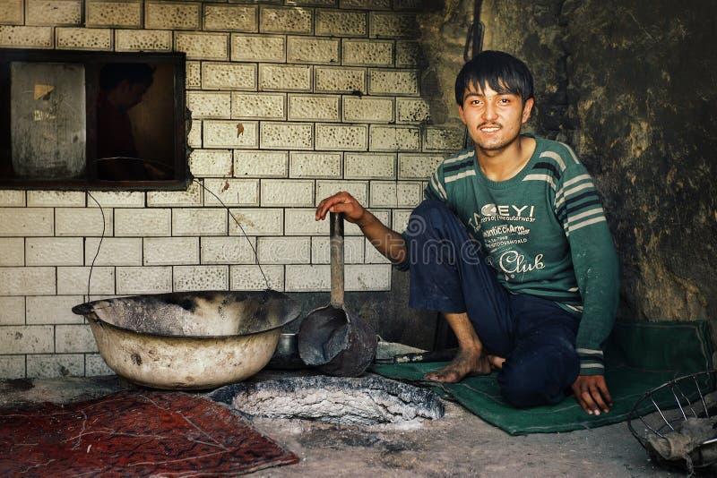 lokalnego uyghur mężczyzna wypiekowy chleb w tradycyjnym piekarniku przy piekarnią obrazy stock