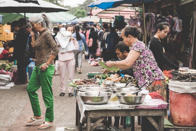 Lokalnej Laotian wzgórza plemienia kobiety buble przy dziennym rankiem i wprowadzać na rynek w Luang Prabang, Laos na 13th LISTOP obraz royalty free